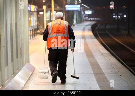 Hamburg, Germany. 06th Nov, 2014. An employee cleans the empty platform at the main station in Hamburg, Germany, - Stock Photo