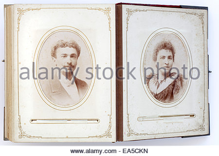 open vintage family photo album from late 1800s with portraits - Stock Photo