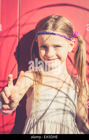 Portrait of smiling little girl in summer showing victory sign - Stock Photo
