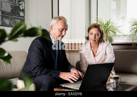 Businessman with laptop talking to woman - Stock Photo