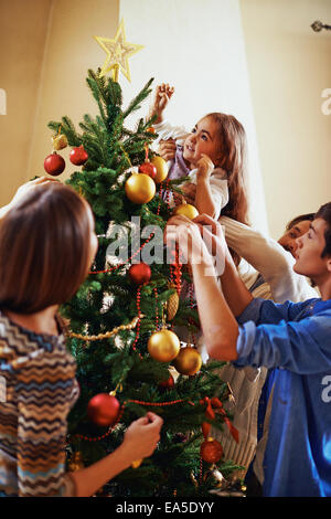 Modern family of four decorating Christmas tree before holiday - Stock Photo