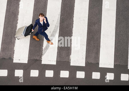 Germany, businesswoman with rolling suitcase walking on zebra crossing, view from above - Stock Photo