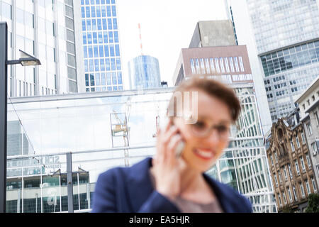 Germany, Hesse, Frankfurt, businesswoman telephoning in front of office buildings - Stock Photo