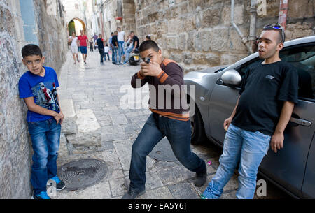 Three young muslim teenagers are playing 'war games' on the streets in the muslim quarter in Jerusalem. - Stock Photo