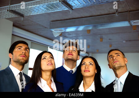 Serious business people looking up with dreaming expression - Stock Photo