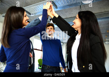 Business team is holding hands together. Raising one hand up - Stock Photo