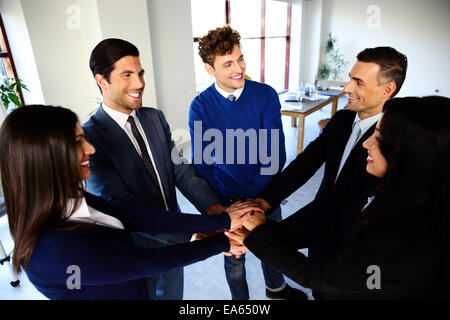 Happy co-workers making pile of hands and looking at each other - Stock Photo