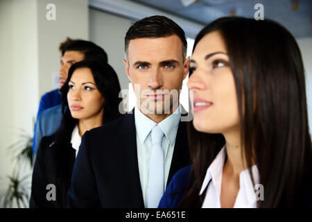 Group of young co-workers standing in a row at office - Stock Photo