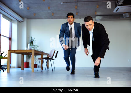Two businessman running together in office. Business concept - Stock Photo