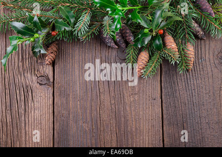 Christmas Tree Branch with Fir Cones over Old Wooden Background - Stock Photo