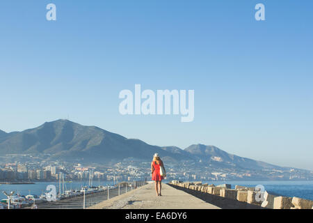 Woman in red walking down pier - Stock Photo