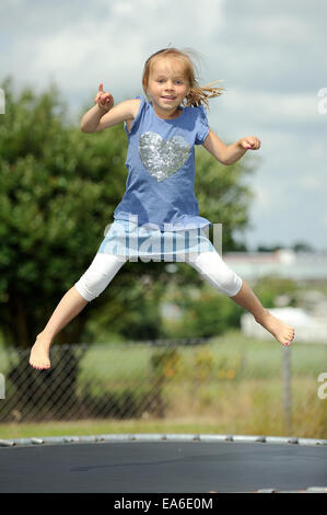 Italia, Calabria, Girl (2-3) jumping on trampoline in summer - Stock Photo