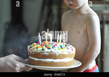 Boy blowing out candles on his birthday cake - Stock Photo
