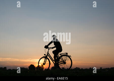 Germany, North Rhine-Westphalia, Cycling at sunset along Rhein River - Stock Photo