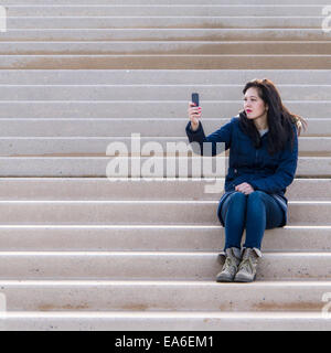 Woman sitting on a step taking a selfie - Stock Photo