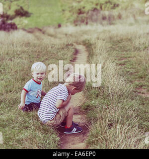Two boys sitting by a footpath - Stock Photo