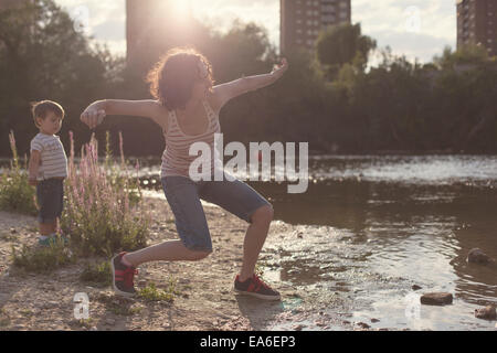 Mother and son standing by a river stone skipping - Stock Photo