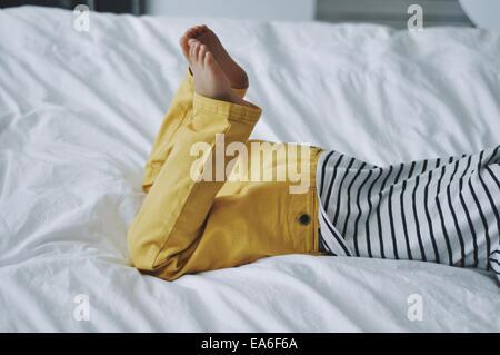 Boy lying on bed - Stock Photo