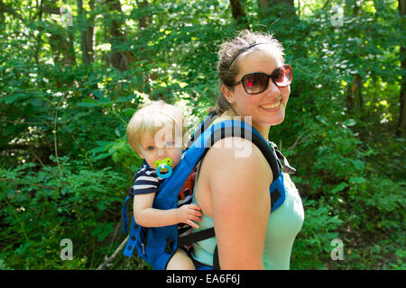 USA, Indiana, Mother and son hiking in woods - Stock Photo