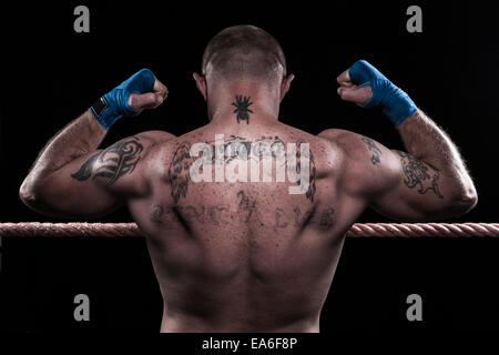 Rear view of a Boxer flexing his muscles in a boxing ring - Stock Photo