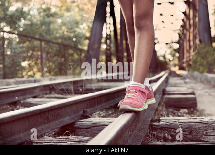 Close-up of woman's legs walking along train tracks - Stock Photo