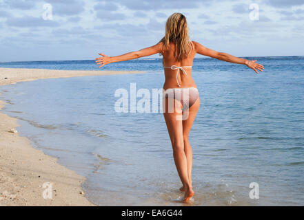 Rear view of Woman walking on beach with arms outstretched - Stock Photo