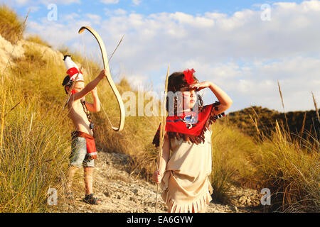 Boy and girl playing dressed up as Indians - Stock Photo