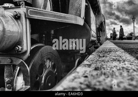 Platform level view of the front of a Bulleid Light Pacific steam loco standing in a platform in black and white - Stock Photo