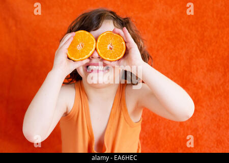 Girl holding oranges in front of eyes - Stock Photo
