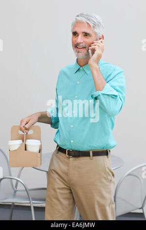 Businessman holding container with coffee cups and talking on mobile phone - Stock Photo