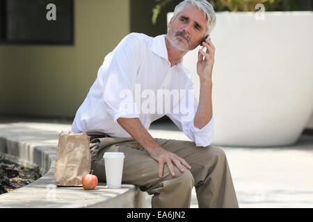 Businessman on lunch break talking on phone - Stock Photo