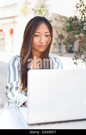 Beautiful asian girl using a laptop, businesswoman or student - Stock Photo