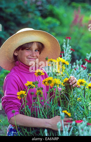 Young girl in a wide-brim straw hat picking flowers in her home garden in New Hampshire, USA. - Stock Photo