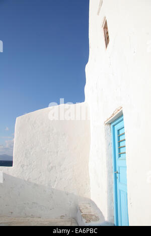 Traditional whitewashed building with blue painted door on a beautiful sunny day, Mykonos town, Cyclades, Greece. - Stock Photo