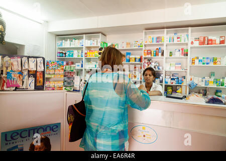 A woman shopping in a chemist pharmacy, Belle Mare village, Mauritius - Stock Photo