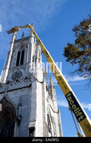 A tall cherry picker and access platform servicing St Peters church tower, Brighton - Stock Photo