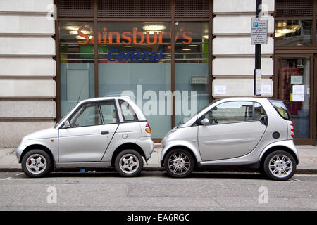 Two small cars, one electric and one petrol from different manufacturers parked in a single parking space in Mayfair - Stock Photo