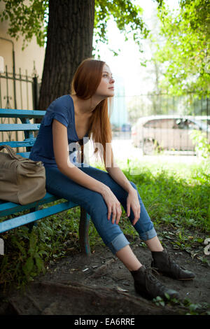Sad Woman Sitting On A Bench Arms Around Her Bended Legs