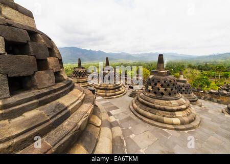 Latticed stone stupas containing Buddha statues on the upper terrace, Borobudur Temple Compounds, Central Java, - Stock Photo