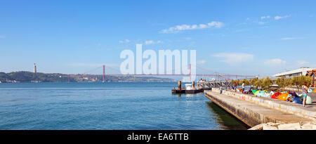 The new Ribeira das Naus area in Lisbon with a view over the Tagus River, the 25 de Abril bridge and the Cristo - Stock Photo