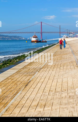 The new Ribeira das Naus area in Lisbon with a view over the Tagus River and the 25 de Abril bridge - Stock Photo