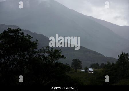 A single car drives in the rain along the road out of Glen Nevis in the Scottish Highlands, Scotland, UK - Stock Photo