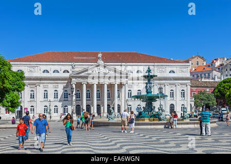 Lisbon, Portugal. Dona Maria II Theatre, one of the fountains and the typical cobblestone pavement in Dom Pedro - Stock Photo