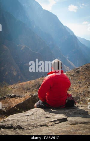 A man sits on a rock ledge overlooking the mountains of Leaping Tiger Gorge; Lijiang, Yunnan Province, China - Stock Photo