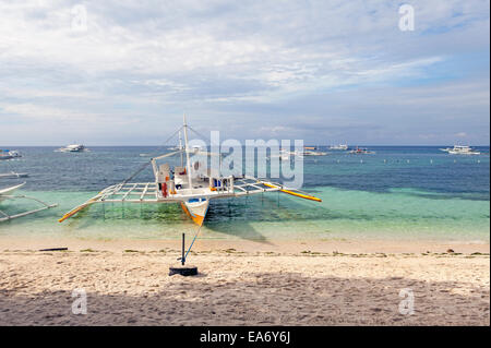A scuba diving fully equipped outrigger sailing boat is anchored at Alona Beach on Panglao Island, Bohol, Philippine - Stock Photo