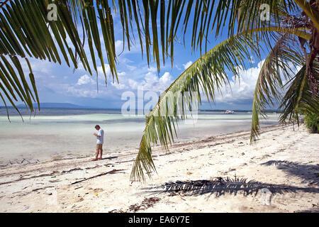 Vacationing tourist beachcombing along a remote, white sand beach on Panglao Island, Bohol, Philippines. - Stock Photo