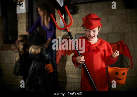 Halloween Party With Children Trick Or Treating In Costume - Stock Photo