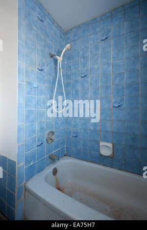 A retro and grimy shower and bathtub with blue tiles in an abandoned house.  Near Oakville, Ontario, Canada. - Stock Photo