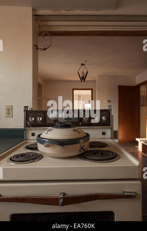 A vintage stove with a crock pot sitting on top found in an abandoned house.  Near Oakville, Ontario, Canada. - Stock Photo