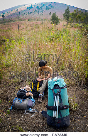 A woman and her puppy doll take a rest during Mount Guntur climbing in West Java. © Reynold Sumayku - Stock Photo
